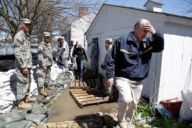Missouri Gov. Jay Nixon, right, walks away from floodwaters after meeting with members of the Missouri National Guard as they make flood preparations on 20 April 2013 in Clarksville. Communities along the Mississippi River and other rain-engorged waterways are waging feverish bids to hold back floodwaters that may soon approach record levels. Photo: Jeff Roberson / The Associated Press