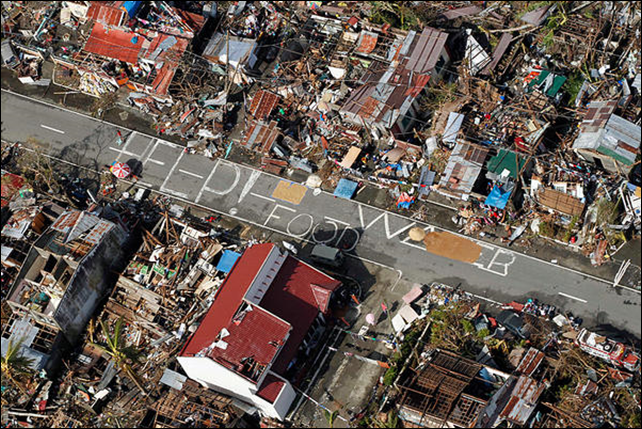 An aerial view shows signs for help and food amid the destruction left from Typhoon Haiyan in the coastal town of Tanawan, central Philippines, Wednesday, 13 November 2013. Typhoon Haiyan, one of the strongest storms on record, slammed into six central Philippine islands on Friday leaving a wide swath of destruction and thousands of people dead. Photo: Wally Santana / AP