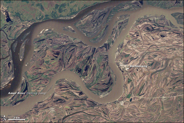 This Landsat 5 satellite image shows the Amur/Heilong River on 19 September 2010. The flood plain is covered by intertwined channels cut during previous floods. Because of the nature of the flood plain, water can linger for a long time. In this image, some of the old channels still hold water, which appears nearly black in this scene. Photo: Jesse Allen and Robert Simmon, using Landsat data from the USGS