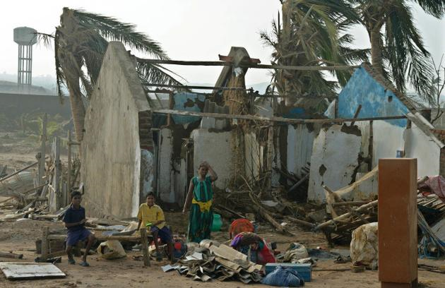 In this 13 October 2013 photo, family hit by Cyclone Phailin is seen near their damaged house, at Gopalpur in Odisha. Photo: K.R. Deepak / The Hindu