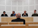 A photo of four panelists speaking while an audience member watches attentively