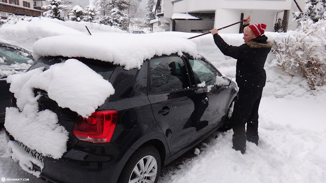 removing snow from car in Seefeld, Tirol, Austria