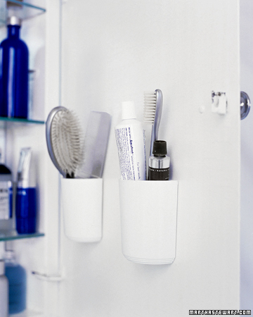 Combs, brushes, and toothpaste take up considerable space when laid horizontally on a shelf. Flat-backed, self-adhesive cups on the inside of the cabinet door hold them more efficiently.