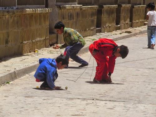 Kids spinning tops in Tarabuco