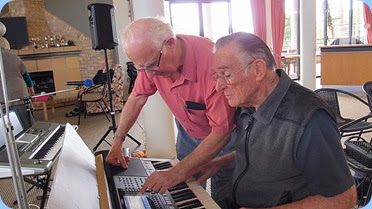 Peter Jackson helps Roy Steen set-up the Yamaha keyboard before Roy played for the audience. Photo courtesy of Dennis Lyons