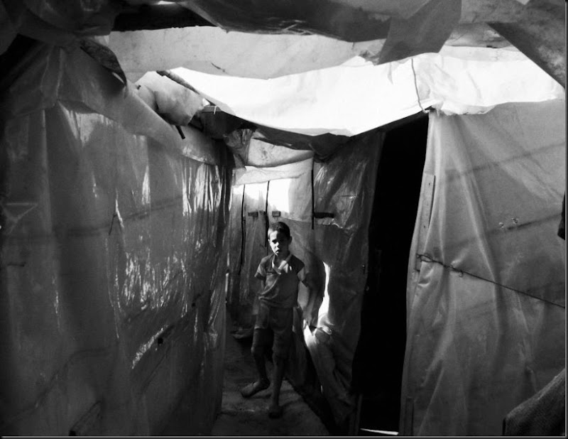 A Syrian boy inside a tent settlement in northern Lebanon. (Moises Saman/Magnum Photos for Save the Children)