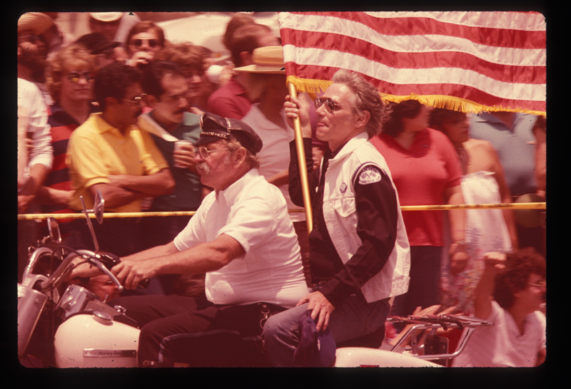 Two men on a motorcycle with an American flag in the Los Angeles Christopher Street West pride parade. 1982.