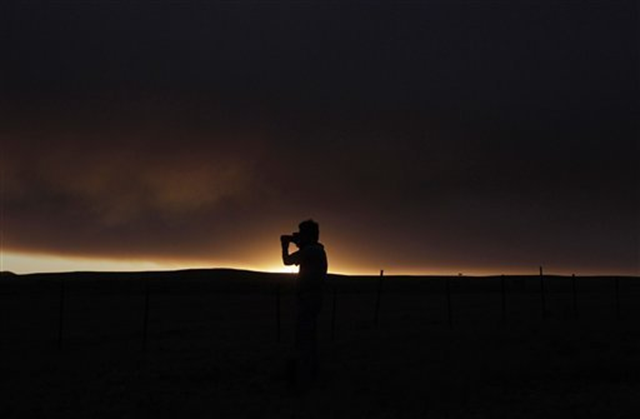 Freelance photographer Thomas Gaulke, of Germany, photographs smoke from the Wallow Fire near Springerville, Ariz., Friday, June 10, 2011. The major wildfire in Arizona's eastern mountains burned out of control early Friday after charring more than 603 square miles of timber, destroying dozens of structures and keeping thousands of evacuees away from their homes. Jae C. Hong / AP Photo