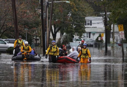 People are evacuated from a neighborhood in Little Ferry, New Jersey, on 30 October 2012, after Hurricane Sandy slammed into the East Coast. Growing public concern over the global warming threat was laid out in a recent study by the Rasmussen Institute. phys.org