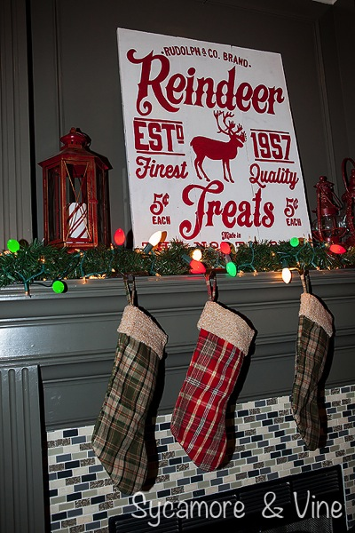 Plaid stockings on mantel with large bulbs and Reindeer Treats Sign.A truly stunning Christmas Home Tour as part of the Christmas in the Country Blog Tour. This Plaid Inspired Country Christmas will knock your socks off. Features tours of the Living room, Dining Room and a Cocoa hot chocolate bar in the Breakfast room. There is so much inspiration for Christmas decorations in this one post. Be prepared to feel like you are cuddled up by the fire in a warm Northwoods comfy cottage! #country #Christmas #Plaid #Holiday decorating #Holiday ideas #Holidays #Christmas decor #Holiday decor