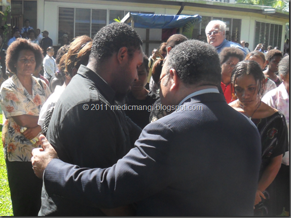 John Paul Matlam (left) being consoled by Prime Minister O'Neil, after the memorial mass