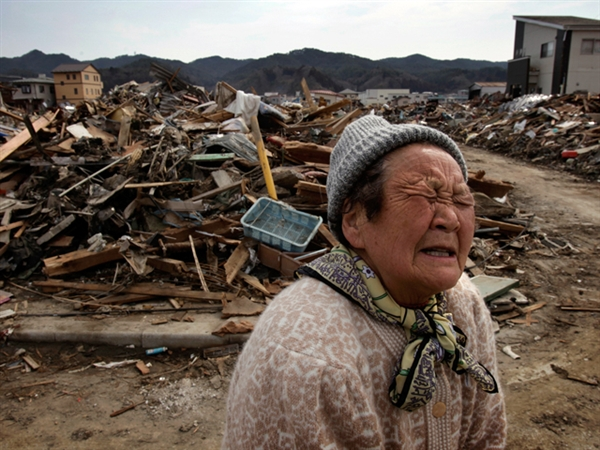 A woman whose house was washed away weeps on 29 March 2011 as she talks about the disaster that befell her hometown of Kesennuma, Miyagi prefecture. Kuni Takahashi