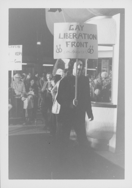 "Man holding a sign that reads ""Gay Liberation Front Los Angeles"" at a protest of the movie ""Boys in the Band."" Circa 1970-1971."