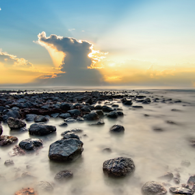 Slow shutter seascape with black stone when sun rising over sea by Shahril Khmd - Landscapes Sunsets & Sunrises ( nobody, skyline, bright, stone, yellow, sky, nature, dark, sunshine, slow, light, black, orange, contour, twilight, horizon, sunlight, dusk, magic, dawn, shutter, wave, golden, calm, reflection, ray, ocean, landscape, coastline, sun, coast, fantasy, mirror, sunny, dramatic, cloudy, long exposure, evening, water, abstract, heaven, sea, hour, morning, color, blue, sunset, outdoor, cloud, sunrise )
