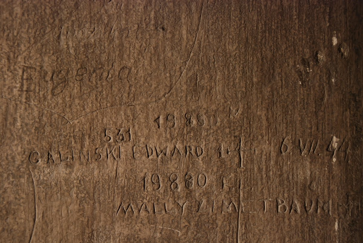 "Fragment of the wall from cell 20 in the basement of Block 11 of the former Auschwitz I camp. Escapee Edward Galiński was held in this cell after his capture, and he was probably the author of the inscription: ""531 Galiński Edward + 6.VII.1944r. 19880 Mally Zimetbaum +."" The inscription includes the names and prisoner numbers of the escapees, as well as the date they were captured: July 6, 1944."