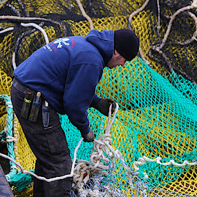 Sewing up the net by Capt Jack - People Professional People ( cold, alaska, wor, tired, tough, fishing, fisherman, net, rugged, smart, dutch harbor )