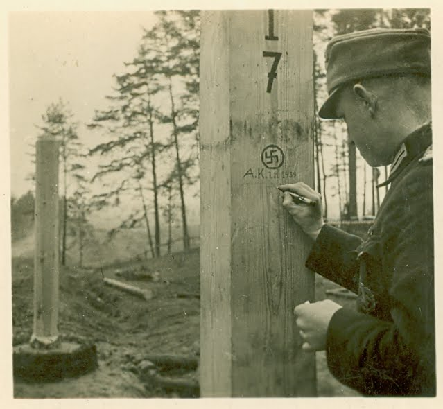 German soldier marking a border post on the German-Soviet demarcation line.