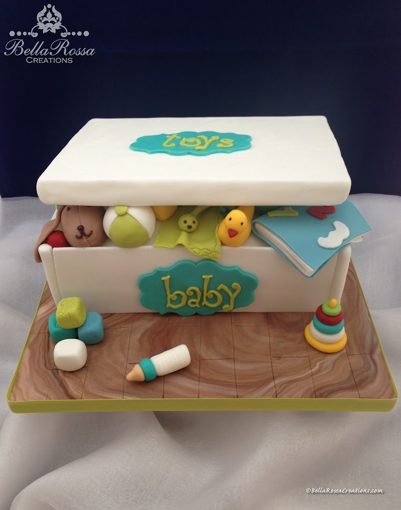 As a cake designer, there is always a new theme or design that you hope someone will order soon. This toy box cake was one of them, decorated with gum paste figurines to celebrate a Baby Shower.