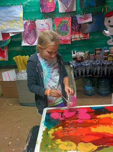 Teen student creating an abstract 'glass' painting using colored resin