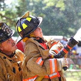 Fireman teaching his son the craft by Tony Powers - People Family ( fireman, fire fighter, father son, fire controlled burn )