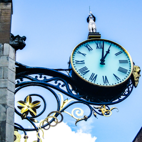 Ornate clock by Del Candler - Buildings & Architecture Architectural Detail ( trumpeter, blue sky, ornate, clock, wrought iron, gold, black, object )