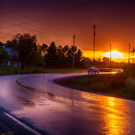 Drive off into the Sunset.  Crazy skies on our way home. by Trish Golden - Landscapes Sunsets & Sunrises