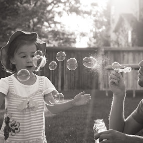 Blowing bubbles in the golden hour by Denise Johnson - Black & White Street & Candid ( girl, black and white, bubbles, candid, man, golden hour,  )