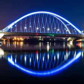 Eye of the City by Evan Miles - Buildings & Architecture Bridges & Suspended Structures ( water, reflection, d3200, architecture, 18-55mm, glow, lowry ave, city, color, minneapolis, kit lens, long exposure, night, bridge, nikon, river )