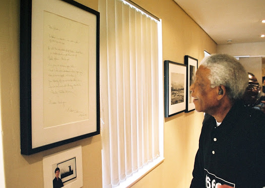 Mandela listens attentively to the explanation offered by the project manager, Verne Harris. In attendance is photographer Matthew Willman.