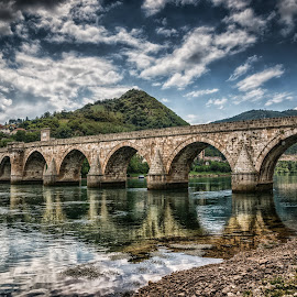 Bridge on Drina by Dobrinovphotography Dobrinov - Buildings & Architecture Bridges & Suspended Structures ( drina, old, famous place, mountain, europe, arch, ivo, stone, architecture, united nations educational, visegrad, bosnia and hercegovina, traditional culture, aging process, andric, style, restoring, travel locations, ottoman empire, social history, historic world event, journey, landscaped, sokolovic, recovery, riverbank, architecture and buildings, history, serbia and montenegro, urban scene, islam, serbia, cuprija, column, summer, scientific and cultural organization, bridge, day, built structure, waterfront, river,  )