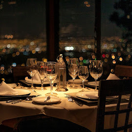 Table with a View by Raymond Pauly - Artistic Objects Cups, Plates & Utensils ( plates, tablecloth, napkins, glassware, city lights, table, view, restaurant, cuttlery )