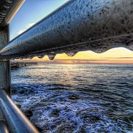 Sunrise through the rails by Mike Whittington - Buildings & Architecture Other Exteriors ( sun sunrise rail rails ocean water sky reflection shine shining )