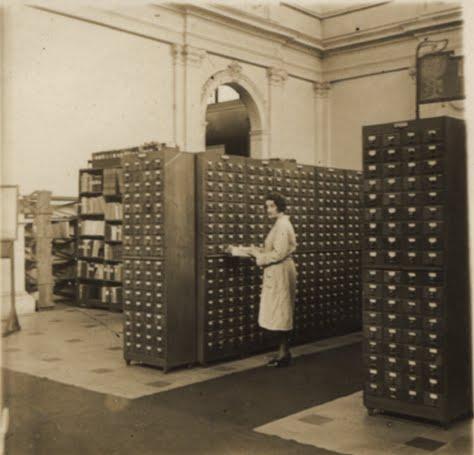 Une employée du Mundaneum occupée à effectuer des recherches dans le Répertoire Bibliographique Universel, installé au Cinquantenaire à partir de 1920