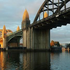 Under the Bridge by Lori Pagel - Buildings & Architecture Bridges & Suspended Structures ( clouds, water, reflection, sunlight, coastal, dusk, coast, sky, drawbridge, sunset, bridge, wet, gold, evening, golden, river )