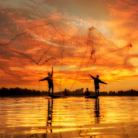 Fisherman of Lake in action when fishing by Sasin Tipchai - People Street & Candids ( laos, fish, thailand, travel, people, asian, bangkok, balance, farmer, nature, province, job, tourism, lake, environment, food, ripple, culture, paddle, reflection, tropical, cultural, sillouette, burma, kayak, landscape, net, mirror, tranquil, poverty, tradition, asia, worker, man, water, peaceful, inle, weed, poor, entrapment, traditional, boat, myanmar, blue, sunset, sunrise, fishing, fisherman, reflect, river )