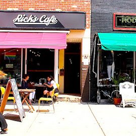 Rick's Cafe by Ronnie Caplan - City,  Street & Park  Neighborhoods ( tables, walking, girl, streetscene, colourful, patio, awnings, restaurant, people, sidewalk )