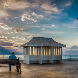 Relaxing in the Sunset by Jan Murphy - Novices Only Landscapes ( ornate, wood, bench, relax, yellow, glow, iron, tranquil, copper roof, shelter, metal, seat, pier, lamp post, evening, man, planks, clouds, orange, peaceful, peach, bald, relaxing, shadows, rays, colours, roof, railings, chair, sitting, window, turquoise, slats, blue, sunset, serene, bulb, lamp, wrought iron, tranquility, seats.,  )