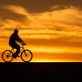 Silhouetted Wheels by Jamie Brown - City,  Street & Park  Street Scenes ( bike, sunset, cycling, portimao, Bicycle, Sport, Transportation, Cycle, Bike, ResourceMagazine, Outdoors, Exercise, Two Wheels )