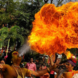 A folklore artist play with Fire to impress public for money in the part of sankranthi celebrations in the city.photograph by Sirige Srikanth. by Srikanth Sirige - News & Events Entertainment