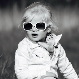 by Evy Ballu - Babies & Children Child Portraits ( girl child, grass, child photography, child portrait, children, beauty, beauty in nature, field trip, sunglasses, looking, looks, blonde, sitting, girl, field flower, girl toddler, fields )