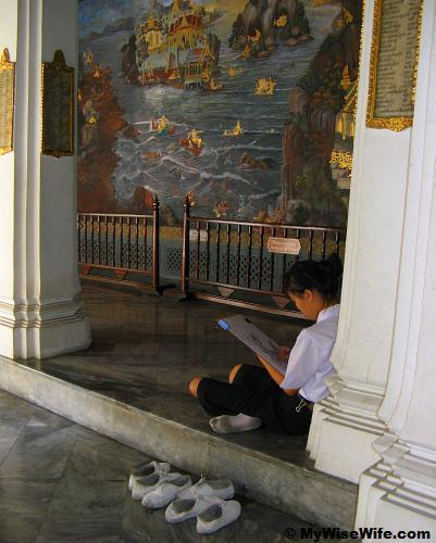 A diligent student by the pillar along the mural