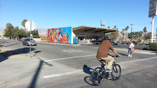 "Originally referred to as the ""Quick N Easy Mural"" in reference to the business' block wall site, the large ""Rebirth"" mural is highly visible along the Indio neighborhood streetscape."