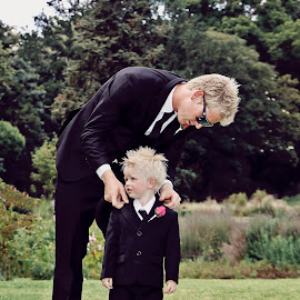 Dad helping son by Alan Evans - Wedding Getting Ready ( wedding photography, melbourne wedding photographer, park, melbourne, botanic gardens, aj photography, getting ready, landscape, melbourne botanic gardens, wedding, pageboy, getting dressed, trees, pink rose, groom, garden )