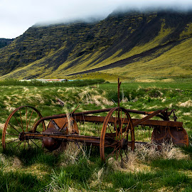 Retired by Lillian Molstad Andresen - Landscapes Mountains & Hills ( hills, sand, may, grass, 2014, retired, moss, landscape, rustic, lava-sand, old machine, mountains, sky, fog, mist )