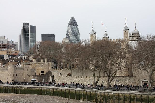 Londýnský Tower při pohledu z Tower Bridge - v dálce je vidět známá budova nazýváná Okurka.