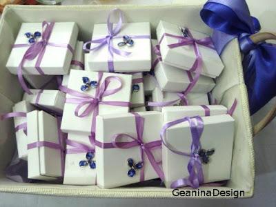 Cos cu cutiile bomboniere albe legate cu panglica lila cu orhidee metalica pictata mov.