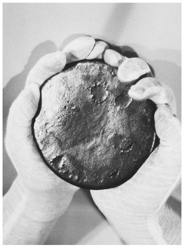 Gloved hands hold a gray lump of uranium. This material has been remolded after having been removed from a Titan II Missile, part of the disarmament after the end of the Cold War.