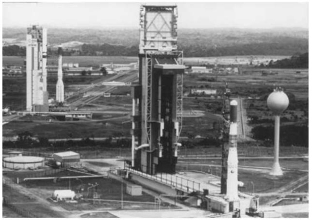 ELA 1 and ELA 2 launch sites. ELA 1 site (foreground): Ariane 3 launcher during third-stage fueling tests on day D — 9. At rear: Ariane 4 launcher recently arrived on the ELA 2 pad. Note the double rail track between the pad and the preparation zone (background). The white circle midway down the rail track is a turntable, used to allow two launchers to pass each other if necessary. This figure is available in full color at http:// www.mrw.interscience.wiley.com/esst.