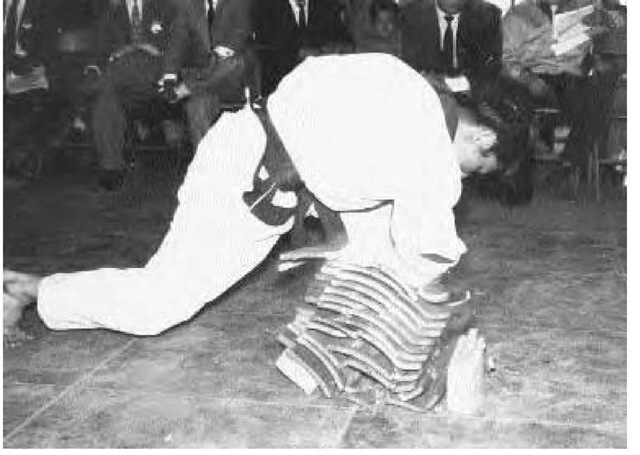 A taekwondo practitioner breaks with his elbow a stack of twelve 1-inch-thick boards, ca. 1950.