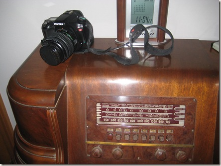 camera sitting on old tube radio